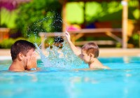 joyful father and son having fun in waterpark pool, summer