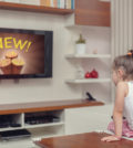cute little girl watching advertisement on tv