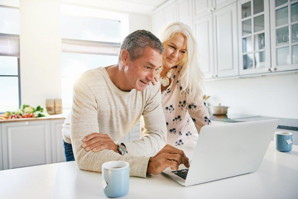elderly-retired-couple-reading-their-social-media-PWCVTD8