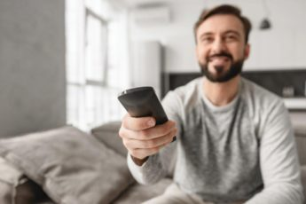 portrait-of-an-excited-young-man-holding-tv-UGBHC9M